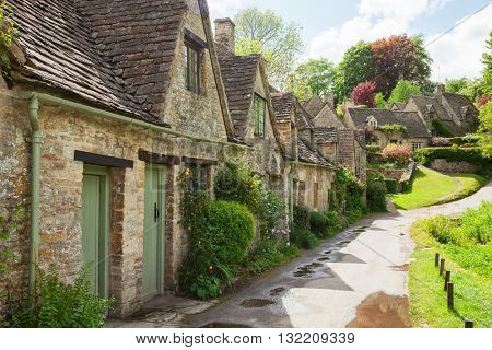 Old street with traditional cottages in  beautiful spring day , Bibury, England, UK.
