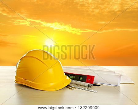 Table with construction drawings and other tools on sunrise background