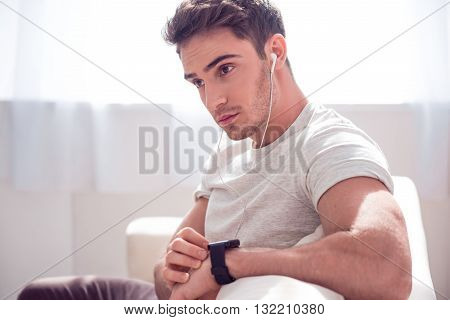 Modern adviser. Delighted brutal handsome man sitting on the couch and touching his smartwatch while listening to music