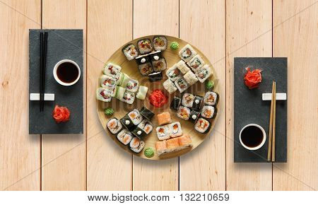 Japanese food restaurant, sushi maki gunkan roll plate or platter set. Set for two with chopsticks, ginger, soy, wasabi. Sushi at wooden planks background. Top view, flat lay.