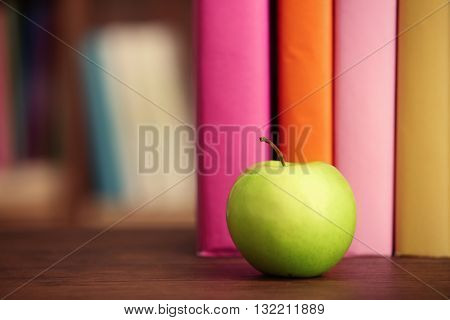 Books and apple on the table, closeup