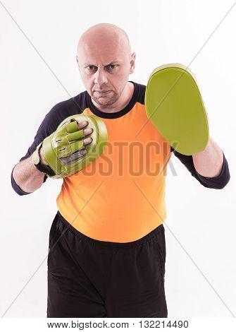 Martial arts trainer holding focus mitts. Studio shoot