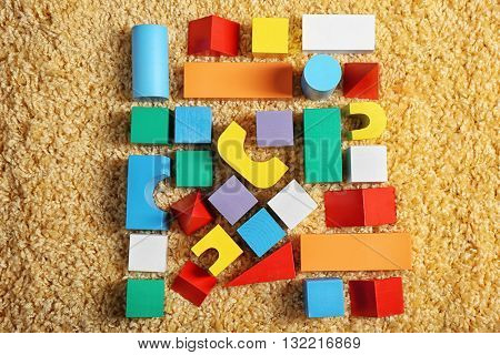 Colorful wooden kids toys on carpet