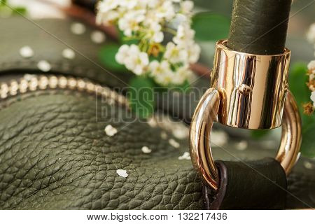 Branch of flowers and detail of green leather handbag
