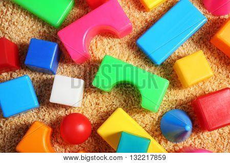 Colorful plastic kids toys on carpet