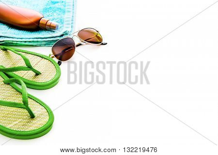Beach accessories. Summer shoes and towel with sunglasses and suntan lotion on a white background