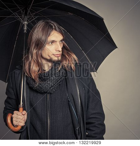 Portrait of handsome fashionable man wearing black coat and scarf holding umbrella. Young guy posing in studio. Winter or autumn fashion. Instagram filter.
