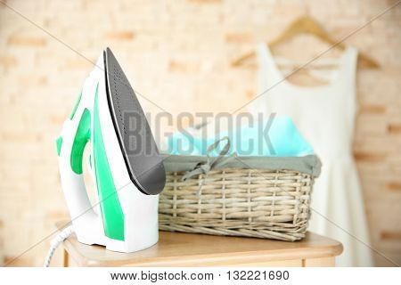Iron and clothes on blurred brick wall background
