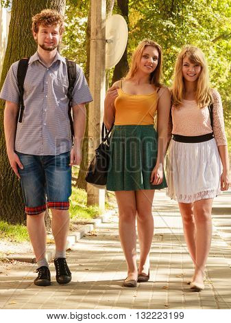 Three people friends walking outdoor. Fashion women and man relaxing enjoying sunny summer vacation.