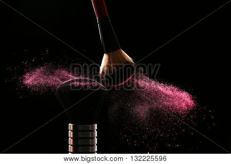 Two make up brushes with powder on black background