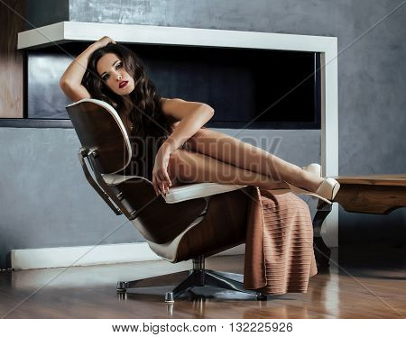 beauty yong brunette woman sitting near fireplace at home, winter warm evening in interior, waiting to celebrate alone