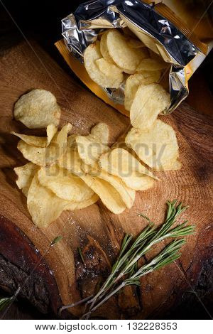 Top view on potato chips with fresh rosemary on wooden board. Open bag of salty snack.