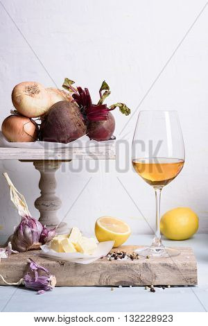 White wine with organic vegetables served on wooden board. Simple rustic style.