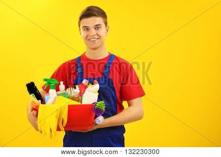 Man holding plastic basin with brushes, gloves and detergents on yellow background