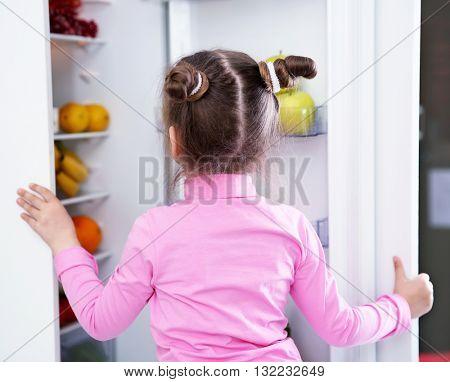 Little girl taking fruits from the fridge