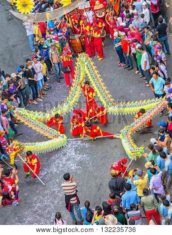 Binh Duong, Vietnam - February 22nd, 2016: Festival dragon dance Lantern yellow winding star shaped control martial arts practitioners on street cheers visitors around tourism in Binh Duong, Vietnam