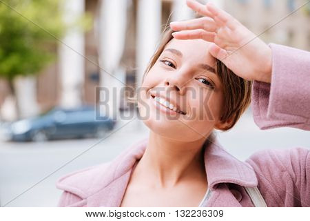 Close-up portrait of a young smiling beautiful girl touching her forehead outdoors