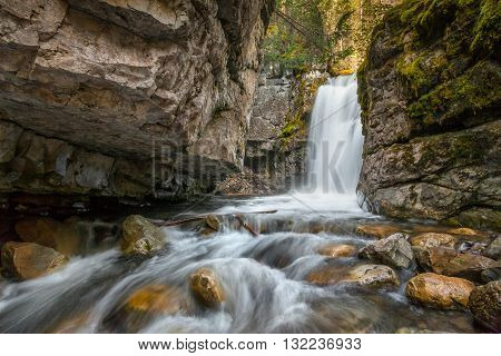 A small waterfall and stream flowing over the rocks through the forest in Kananaskis, Alberta Canadaget the right angle