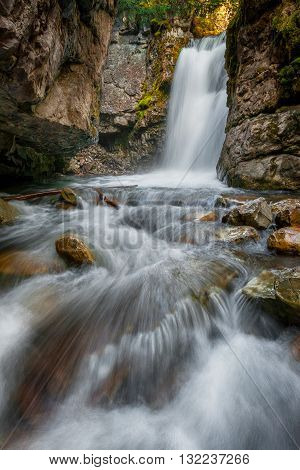 A small waterfall and stream flowing over the rocks through the forest in Kananaskis, Alberta Canada