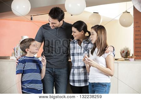 Family Looking At Boy Holding Ice Cream At Parlor