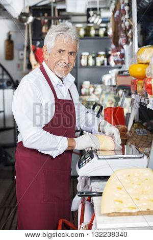 Happy Salesman Wrapping Cheese At Counter In Shop