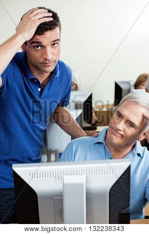 Irritated Teacher With Senior Man Using Computer In Class
