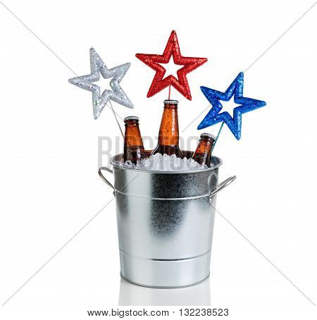 Colorful stars in bucket of ice with bottled beer. Isolated on white with reflection. Fourth of July holiday concept for United States of America.
