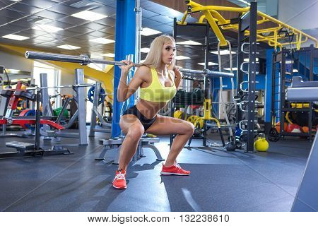 sexy young girl resting after barbell exercises. Fitness blonde woman