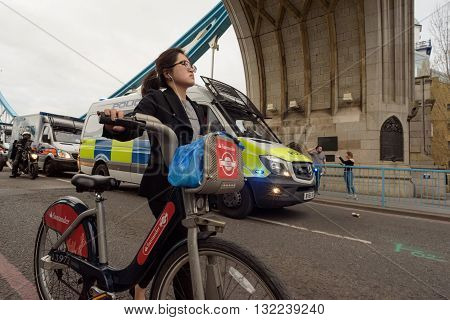 Women With Santander Hire Bike And Police At Tower Bridge