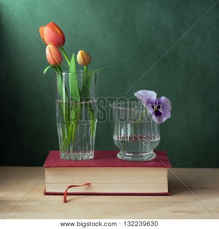 Still life with glass with tulips and glass with pansy.