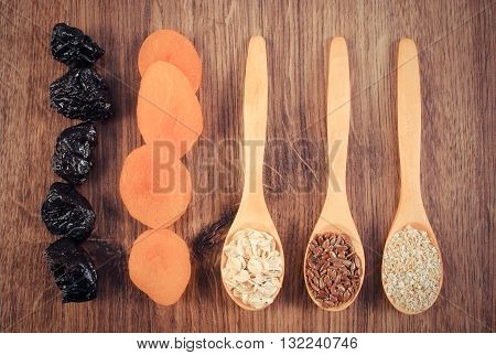 Vintage photo Portion of linseed rye flakes and oat bran on spoon with dried fruits concept of healthy nutrition and increase metabolism ingredients with dietary fiber