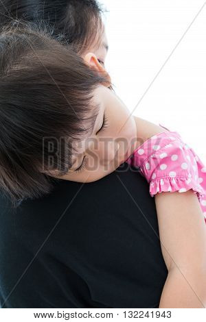 Mother carrying her daughter little asian girl sleeping on mom's shoulder over white background. Mothers Day celebration. Studio shot.