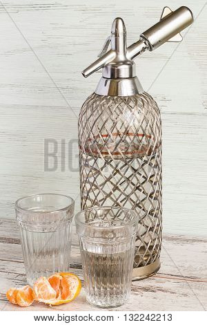 Siphon and two glasses with soda water on a light wooden background.