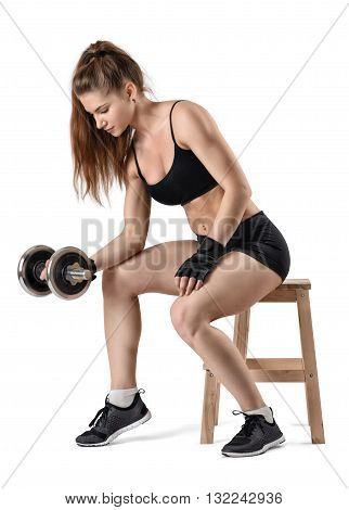 Cutout portrait of muscular young girl sitting on a chair and doing exercises. Power training. Power of body. Fitness and sport. Sportswear for training. Healthy lifestyle.