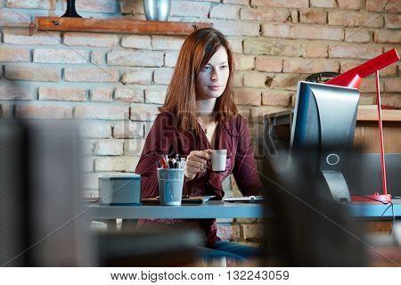 Businesswoman sitting at desk, working on computer.
