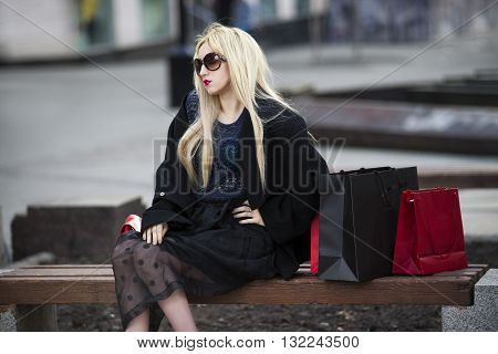 Beautiful young stylish blonde woman in black coat and sunglasses with shopping bags sitting on a bench in the park