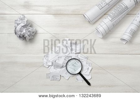 Close-up magnifier is on an architect drawing torn into small pieces and crumpled on a wooden surface. Top view composition. Search of the lost. Detailed search. Workplace of architect or constructor. Engineering work. Failure. Construction and architectu