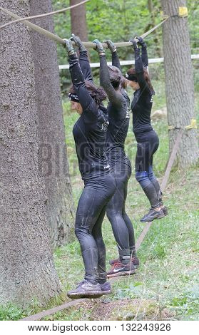 STOCKHOLM SWEDEN - MAY 14 2016: Side view of three woman with mud in their face trying to maintain the balance on a slack rope in the obstacle race Tough Viking Event in Sweden April 14 2016