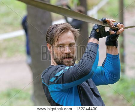 STOCKHOLM SWEDEN - MAY 14 2016: Man trying to maintain his balance on a slack rope in the obstacle race Tough Viking Event in Sweden April 14 2016