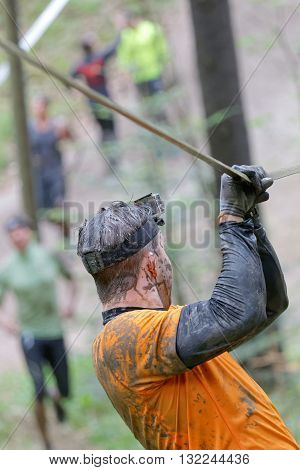 STOCKHOLM SWEDEN - MAY 14 2016: Rear viev of man with mud in his face trying to maintain his balance on a slack rope in the obstacle race Tough Viking Event in Sweden April 14 2016