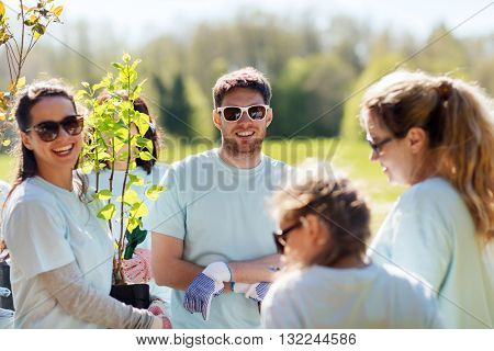 volunteering, charity, people and ecology concept - group of volunteers planting trees in park