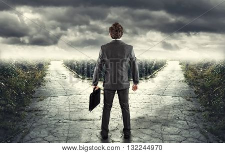 Young businessman in front of a bifurcation - Which path?