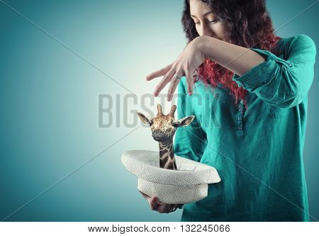Young girl making a magic trick giraffe show up in hat