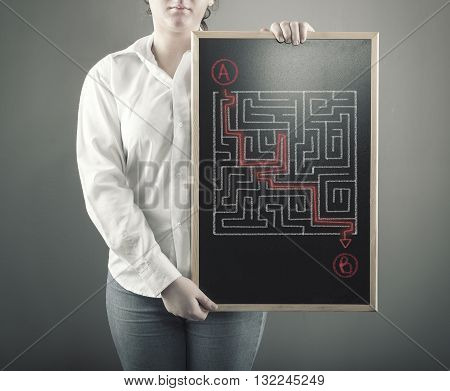 The young girl is considering how to shorten the path through the maze.