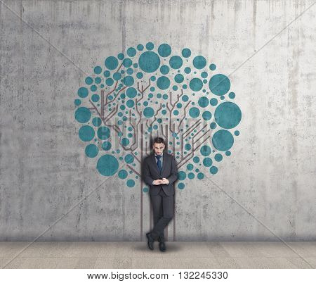 Young businessman using phone and circuit board tree painted on the wall network concept circuit root to a network tree