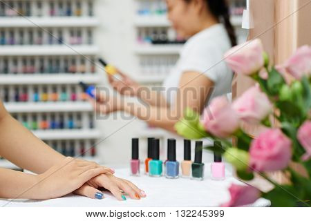 Client waiting when manicurist choosing a color, focus on foreground