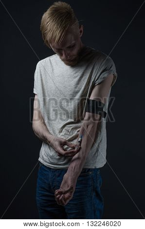Addiction Topic: The Addict Takes Drugs With A Syringe And Pills On A Dark Background