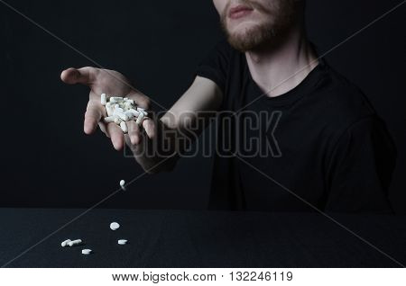 Addiction Topic: The Addict Keeps Tablet With A Drug On A Dark Background