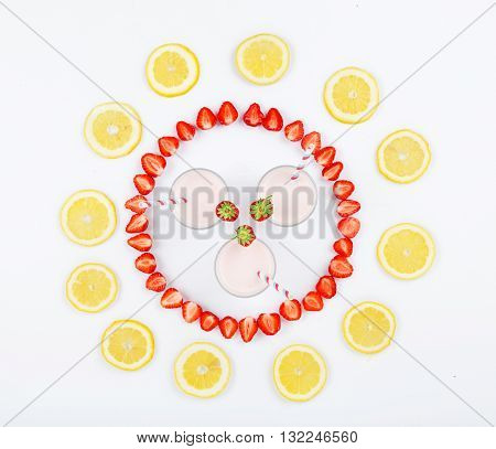 Strawberry smoothies on a white background decorated with slices of strawberry and lemon. Top view. Flat lay