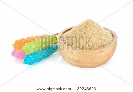 brown sugar in wooden bowl and sugar stick on white background